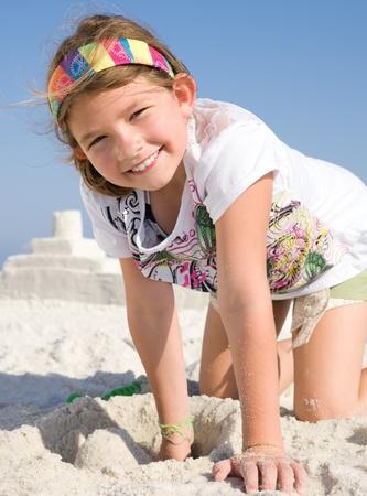 children sandcastle: Happy girl building sandcastle on a beach