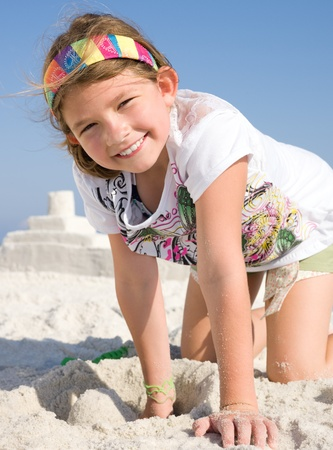 Happy girl building sandcastle on a beach