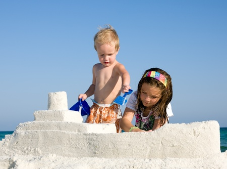 Happy kids building sandcasttle on a beach