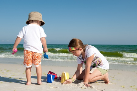 Two kids playing by the ocean with sand   photo