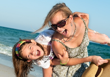 Happy mother and daugterr having fun spending time together on a beach photo