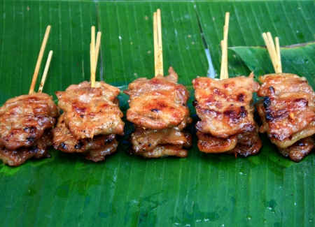 Thai style BBQ pork on banana leaf photo