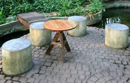 wooden circular table and  cement chairs in a park Stock Photo - 24835141
