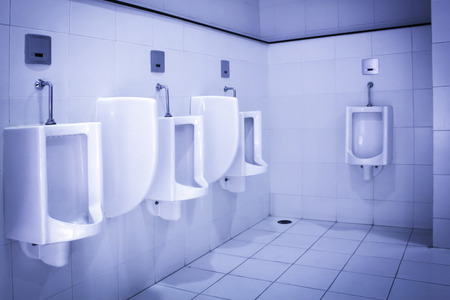 Urinals in public toilet dingy room photo