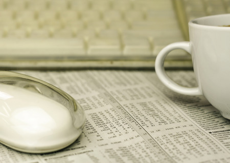 mouse , a cup of coffee and keyboard on a newspaper with a very shallow depth of field with copy space for text photo