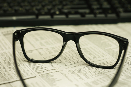 keyboard and a black eyeglasses on a financial newspaper with a very shallow depth of field with copy space for text photo