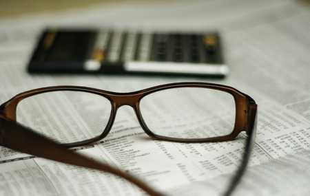 glasses and calculator on newspaper with a very shallow depth of field with copy space for text