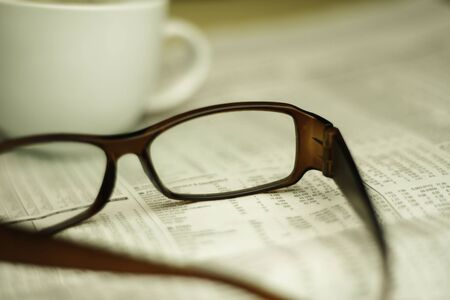 broadsheet newspaper: closeup of glasses on a newspaper with a very shallow depth of field with copy space for text