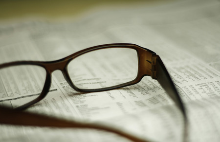 closeup of glasses on a newspaper with a very shallow depth of field with copy space for text photo