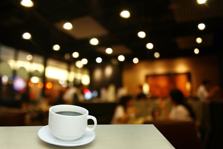 bokeh: Blurred background : white cup of coffee and customer at restaurant blur background with bokeh