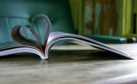 Heart from book pages in blurred background Standard-Bild