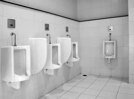 Urinals in public toilet black and white style photo