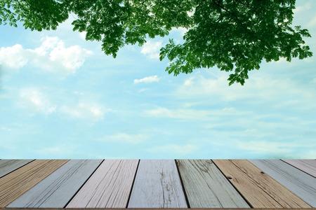 緑の葉と空の背景の木の床