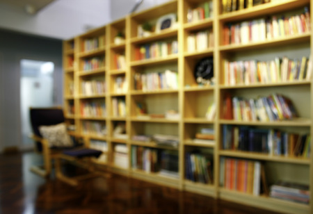 library background: Blurred books on the shelf in public library. Blurred effect. Background for your pictures