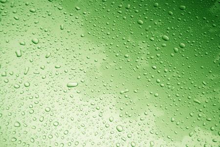 緑のフィルターと背景の車のボディに水滴