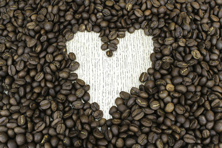 silhouette coeur: Heart shape made from coffee beans on wooden