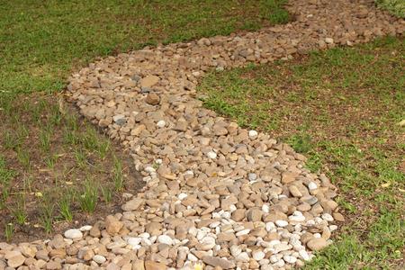 stone wash: Stone wash pebble path on green grass Stock Photo