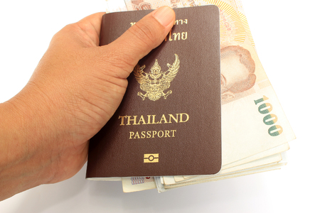 foreign bodies: Thai money and passport in man hand isolated on white