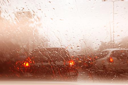 Road view through car window with rain drops, Driving in rain.