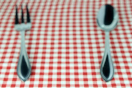 food absorption: Blurred background : Silverware fork and spoon on tablecloth for food serving background