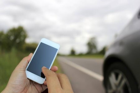 miscarry: hand holding the smartphone on blur of Road running through the way