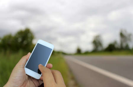 hand holding the smartphone on blur of road running through the way Stock Photo