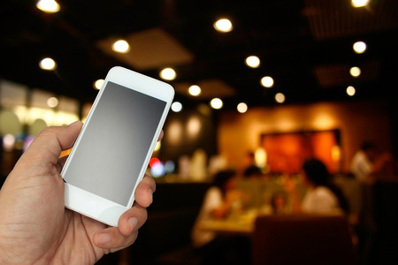 hand holding the smartphone on blur restaurant background,Transactions by smartphone concept