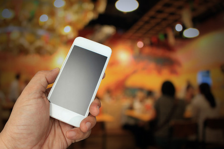 appoint: hand holding the smartphone on blur restaurant background,Transactions by smartphone concept