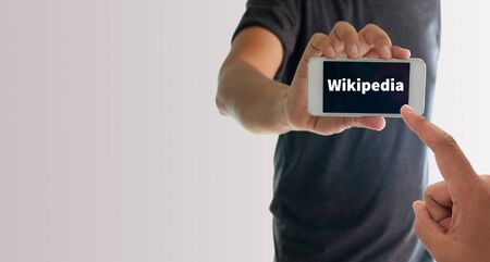 wikipedia: a man using hand holding the smartphone with text wikipedia on display Stock Photo