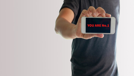 no1: a man using hand holding the smartphone with text you are no.1 on display