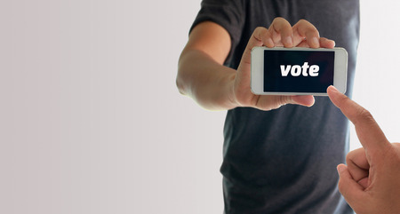 a man using hand holding the smartphone with text vote on display
