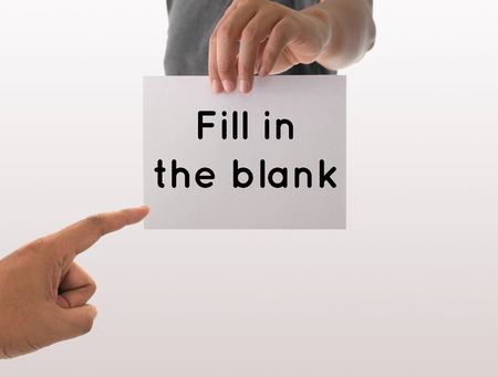 fill fill in: a man using hand holding the white paper with text fill in the blank Stock Photo