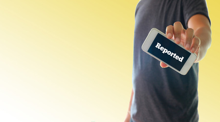 reported: a man using hand holding the smartphone with text reported on display