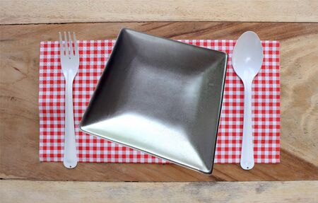 food absorption: plate on tablecloth and spoon with fork for food serving background