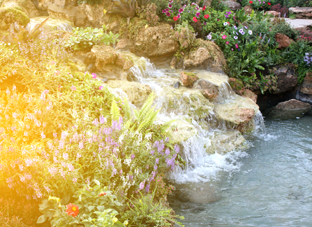 garish: Flowers and waterfall in indoor garden with burst light
