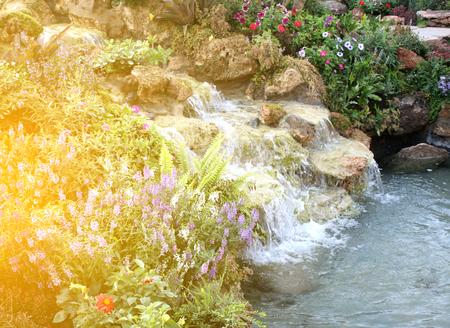 garish: Flowers and waterfall in indoor garden with burst light