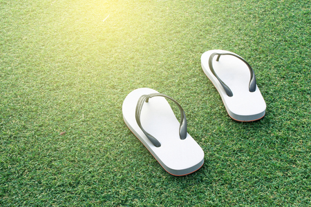 flops: pair of white flip flops in green grass background with burst sunrise light ,dream soft style