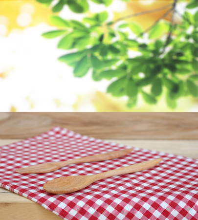 spoon with fork on checkered tablecloth and blur leaves background