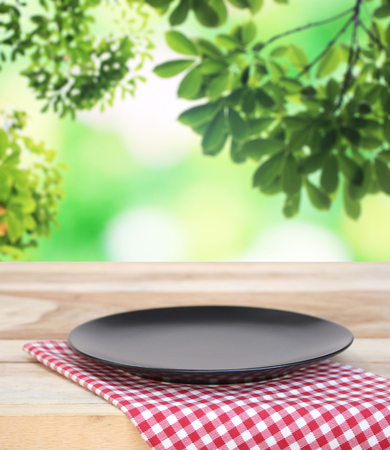 black dish on checkered tablecloth and blur leaves background Stock Photo