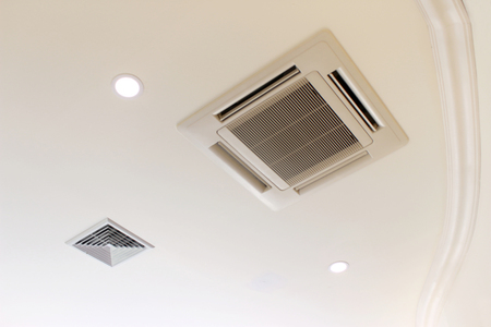 Air conditioner installed on the ceiling of a room Stock Photo
