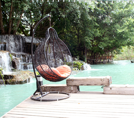 rattan swing chair on waterfront Stock Photo