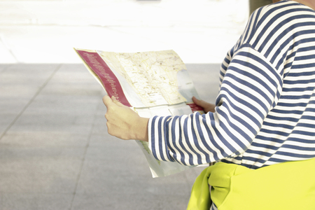 single trip female tourist with suitcase luggage view map for travel on different city in winter , lost alone concept