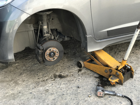 car without wheel and lift up by jack hydraulic waiting for new tire replacement