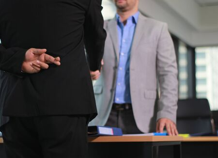 Business man shaking hand with lie sign Stock Photo