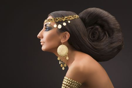 Portrait of the young woman in a profile in east style with a beautiful hairdress and gold ornaments on a black background. photo