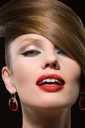 Portrait close-up of the young beautiful woman in earrings with jewels on black background. Stock Photo - 6352033