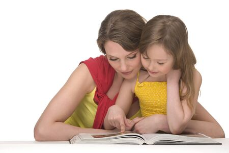 Mum and daughter sit at table and read book Stock Photo - 9746177
