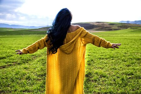 A young woman is watching the sunrise with the arms open in the meadow.