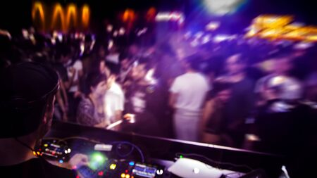 DJ with headphone and dj set at night club party. People at the party are having fun on the background