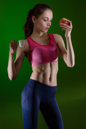 Caucasian girl that chooses to eat sports nutrition or apple. Choice concept.